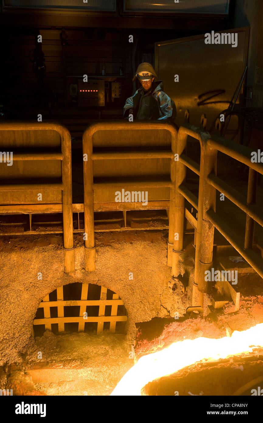 A worker at the outlet of a blast furnace, Duisburg, Germany - Stock Image
