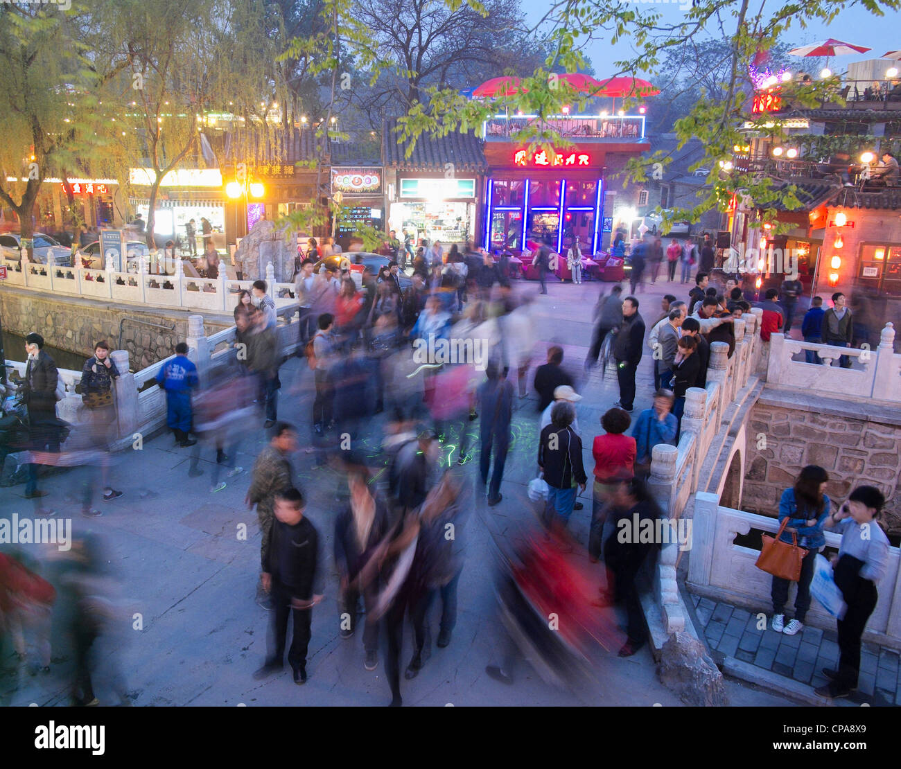 Busy street on historic bridge beside popular tourist location at Houhai Lake in Beijing China - Stock Image