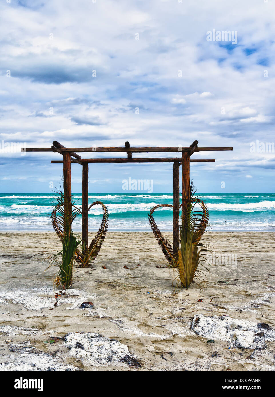 Wedding archway arranged on the sand in preparation for a beach wedding ceremony - Stock Image