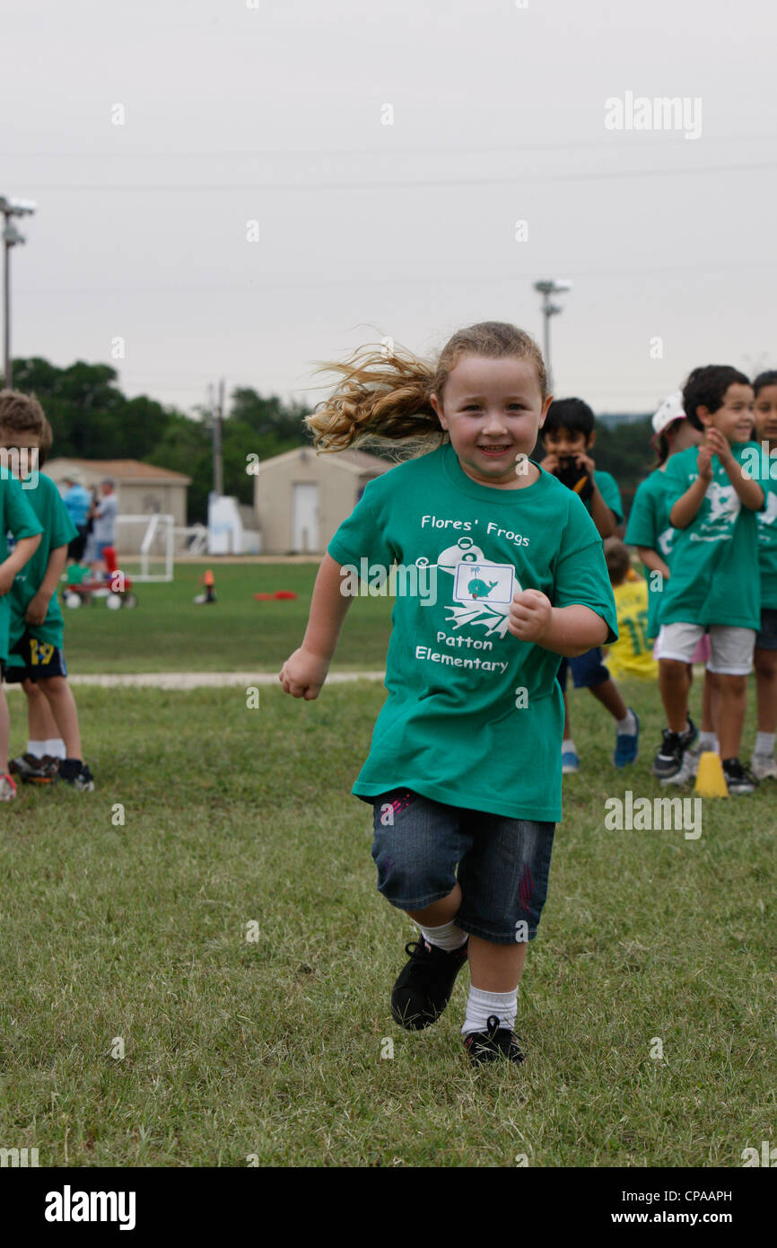 Multi-ethnic kindergarten age school children participate in physical activities outdoors during track and field - Stock Image