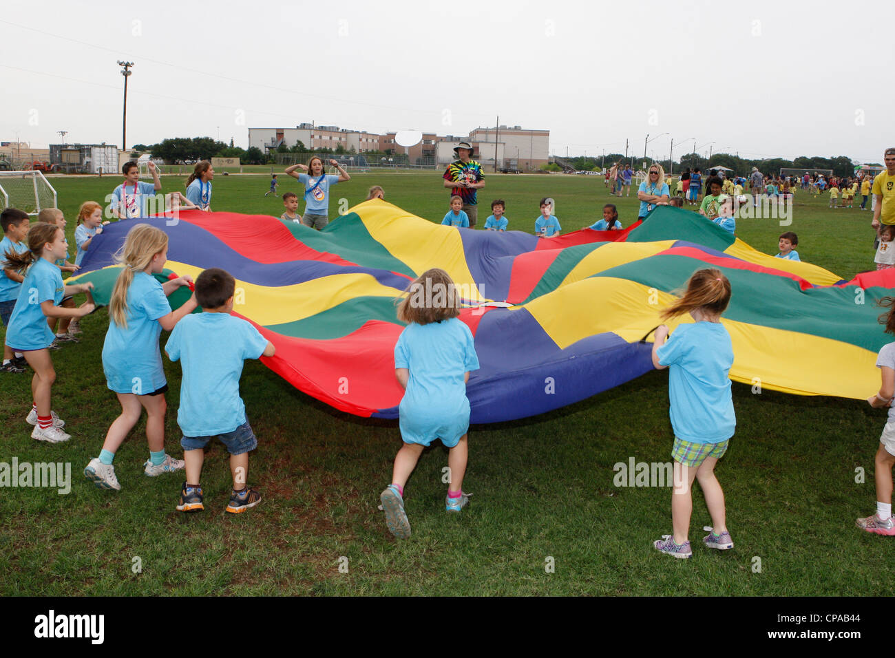 Elementary school age children enjoy lifting the parachute toss during outdoor physical activities at school - Stock Image