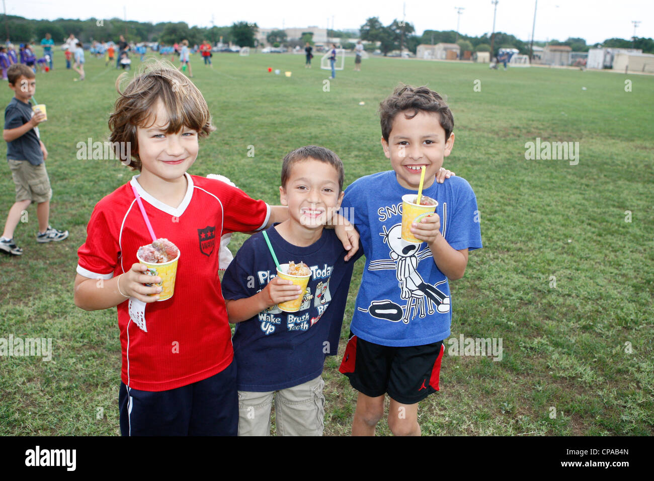 Second grade classmates, show difference in height, while enjoying snow-cones during outdoor activities at elementary - Stock Image