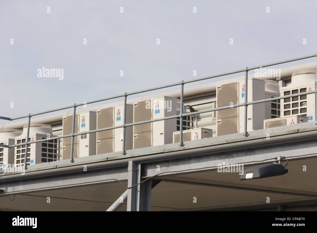 A Row Of Four Mitsubishi Air Conditioning Units On An Exterior Mezzanine  Floor Level Of An