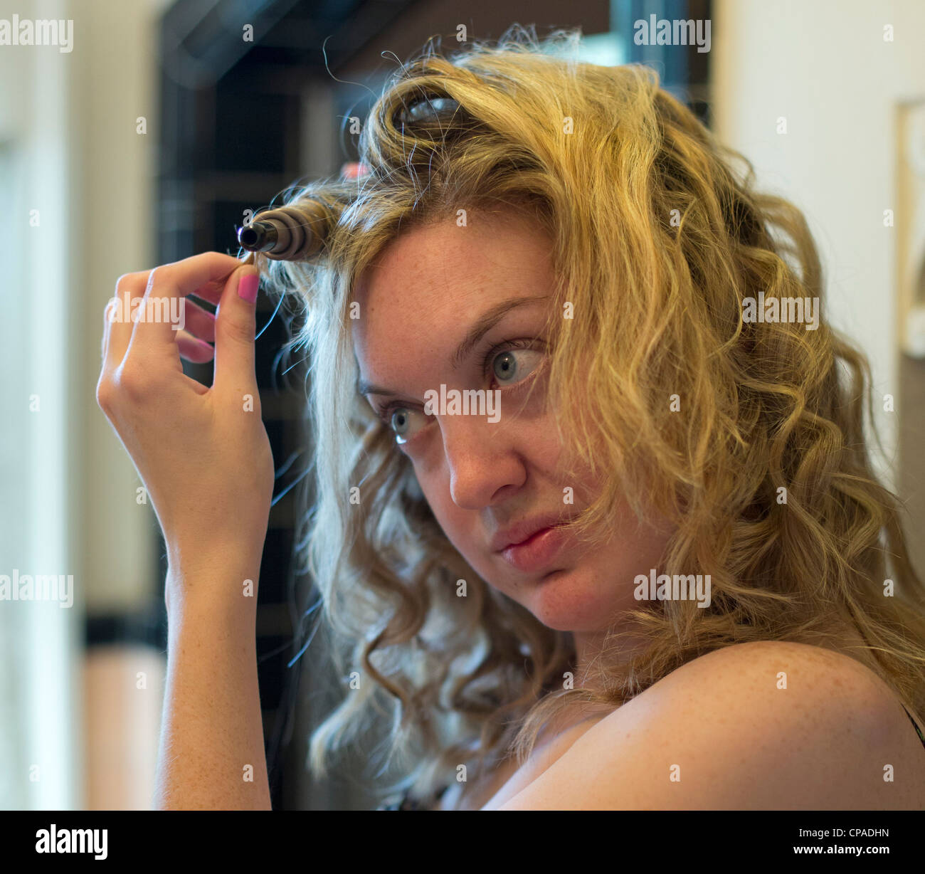 Mariel West, 24, uses a curling iron to curl her hair. - Stock Image