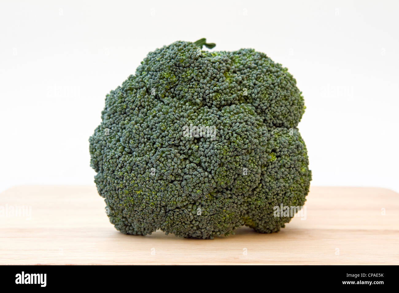 Fresh uncooked broccoli on chopping board - Stock Image