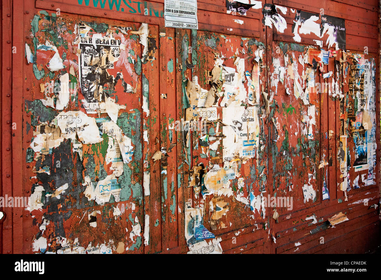 Wall covered in torn fliers in Bogota - Stock Image