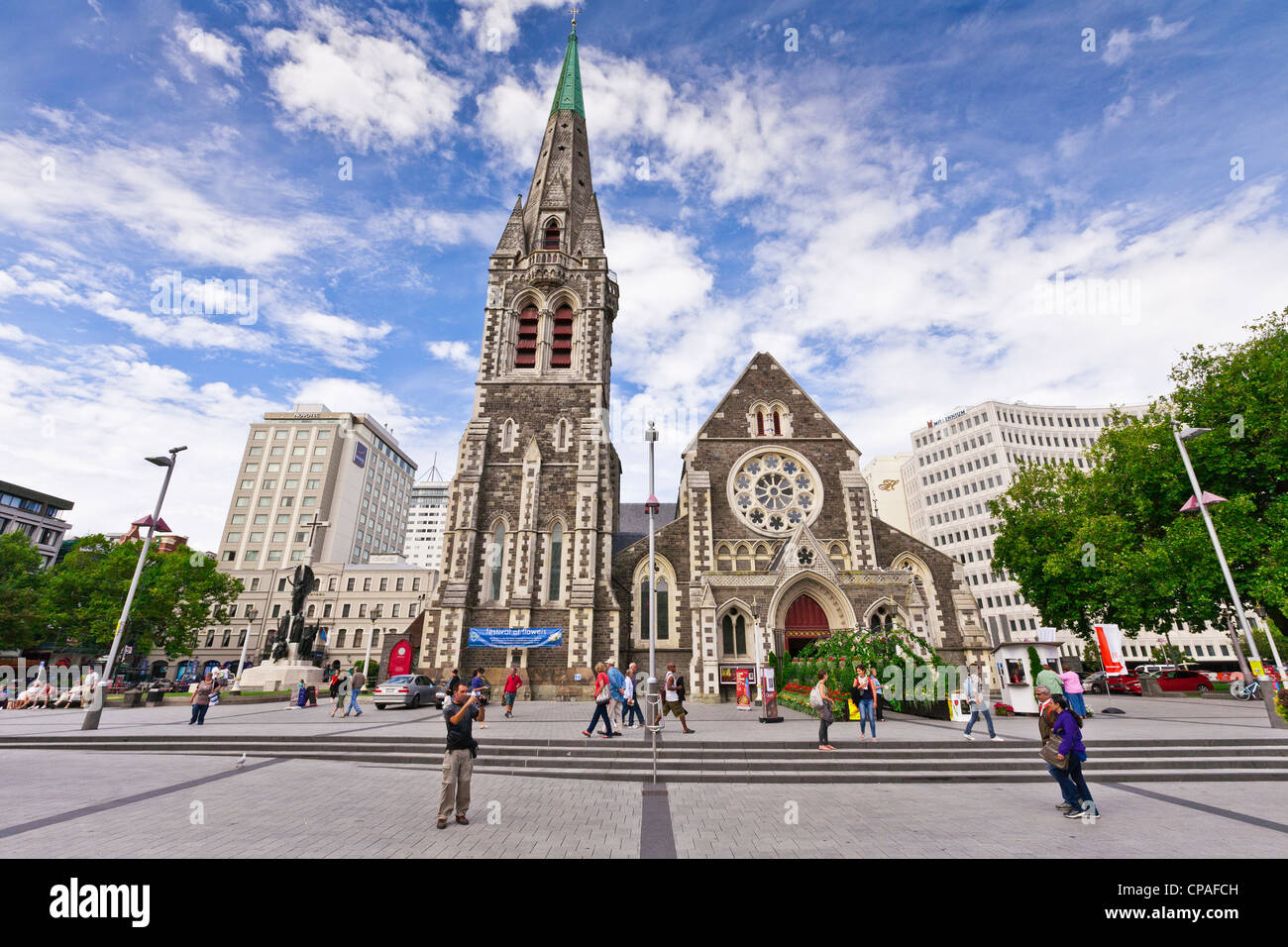 Visitors in Cathedral Square, Christchurch, on a bright overcast day in summer. - Stock Image