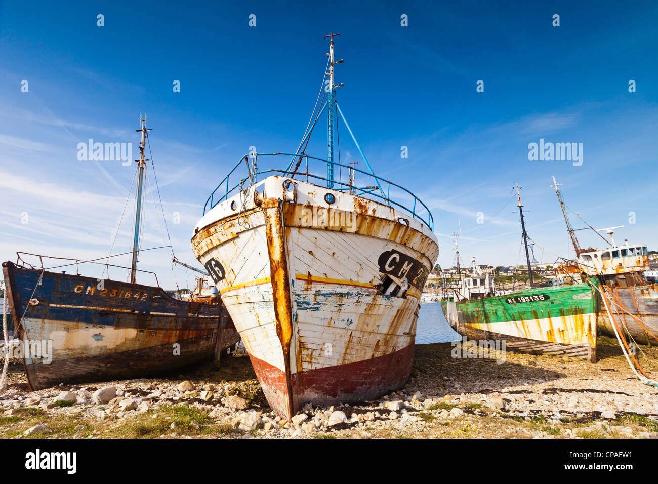 Derelict fishing boats pulled up on a beach at Camaret-Sur-Mer, a holiday resort in Finistere, Brittany, France. - Stock Image