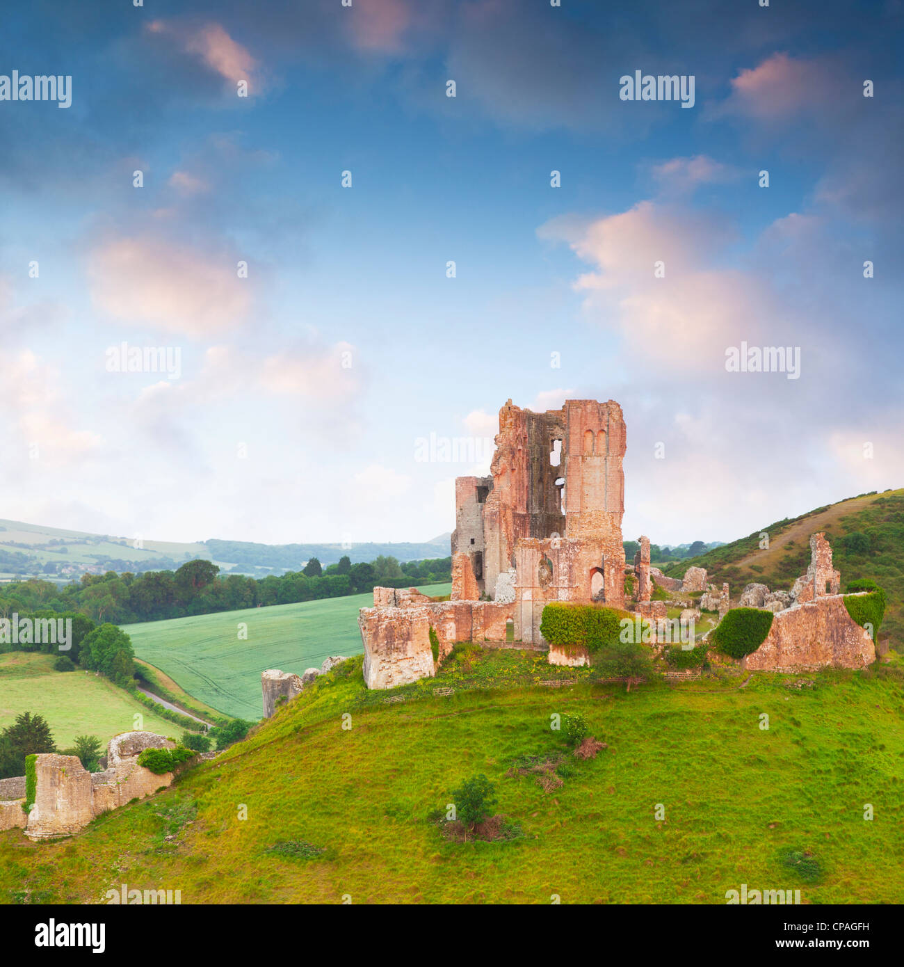 Corfe Castle on its hill above the beautiful Dorset countryside, at sunrise. - Stock Image