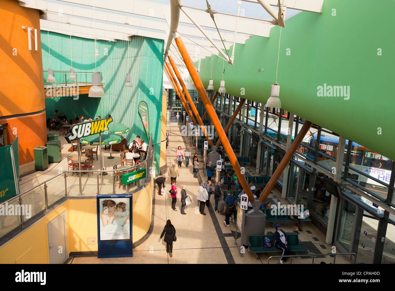 People waiting for buses at Barnsley Interchange, South Yorkshire, England, and a Subway restaurant. - Stock Image