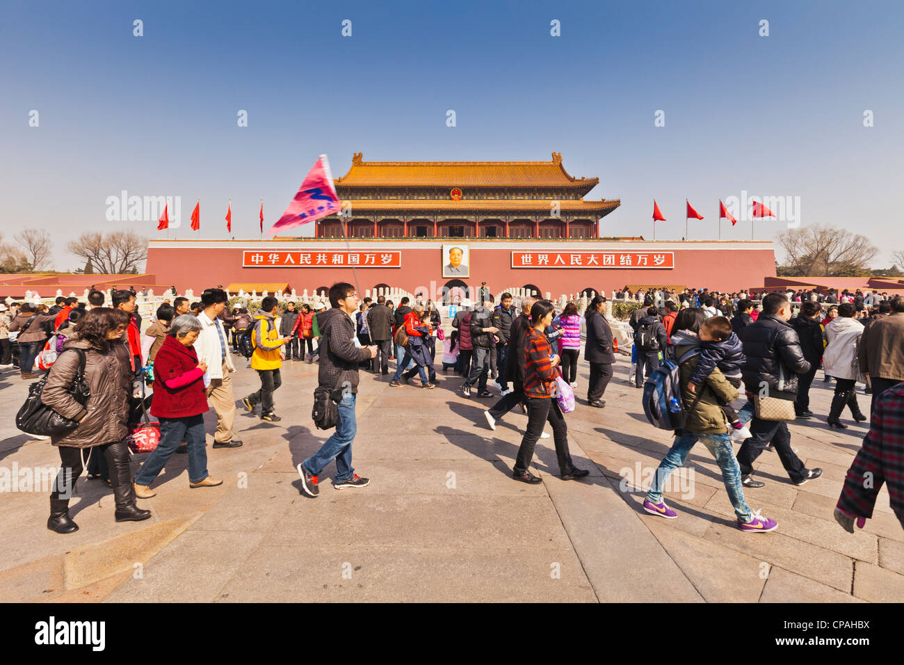 Chinese tourists and tour guide walking outside the Tian'anmen Gate, the Gate of Heavenly Peace, entrance to - Stock Image