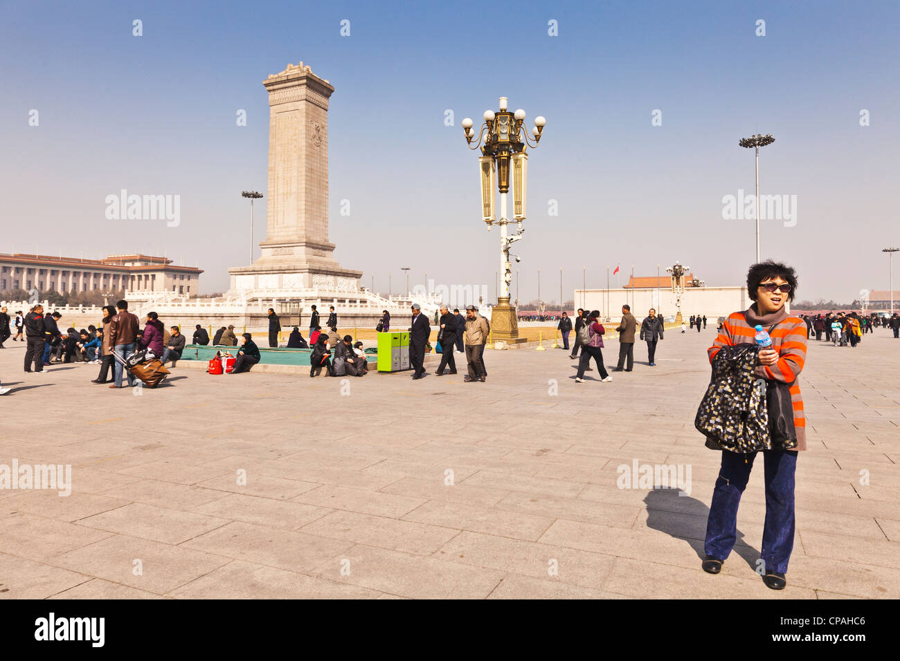 Tourists in Tian'anmen Square, Beijing, China. The obelisk is the Memorial to the Heroes of the Revolution. - Stock Image