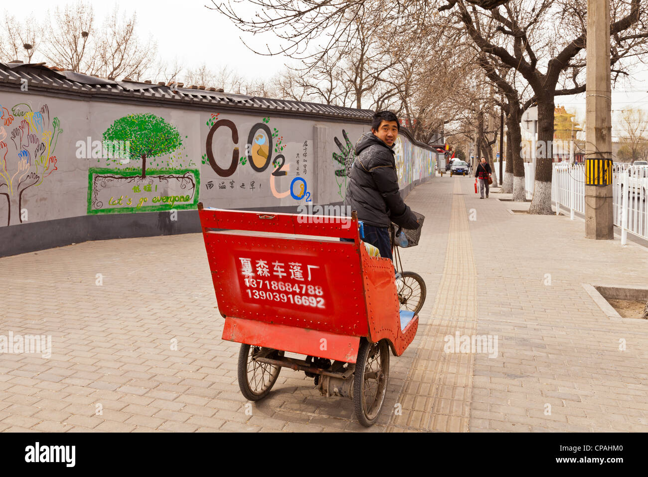 Pedshaw driver looking for business on the streets of Beijing, China - Stock Image