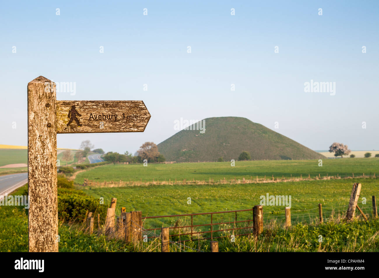 Signpost for footpath to Avebury in Wiltshire, with Silbury Hill, a Neolithic monument, in background. - Stock Image
