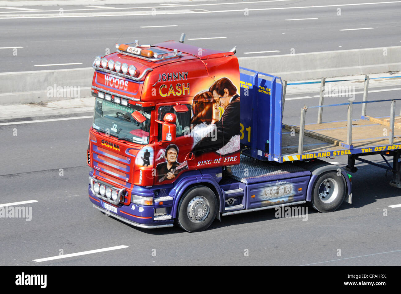 Scania truck with colourful Johnny Cash graphics on side of cab driving along UK motorway - Stock Image