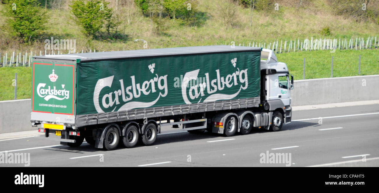 Danish brewer Carlsberg supply chain soft sided articulated curtain delivery trailer and hgv lorry truck driving - Stock Image