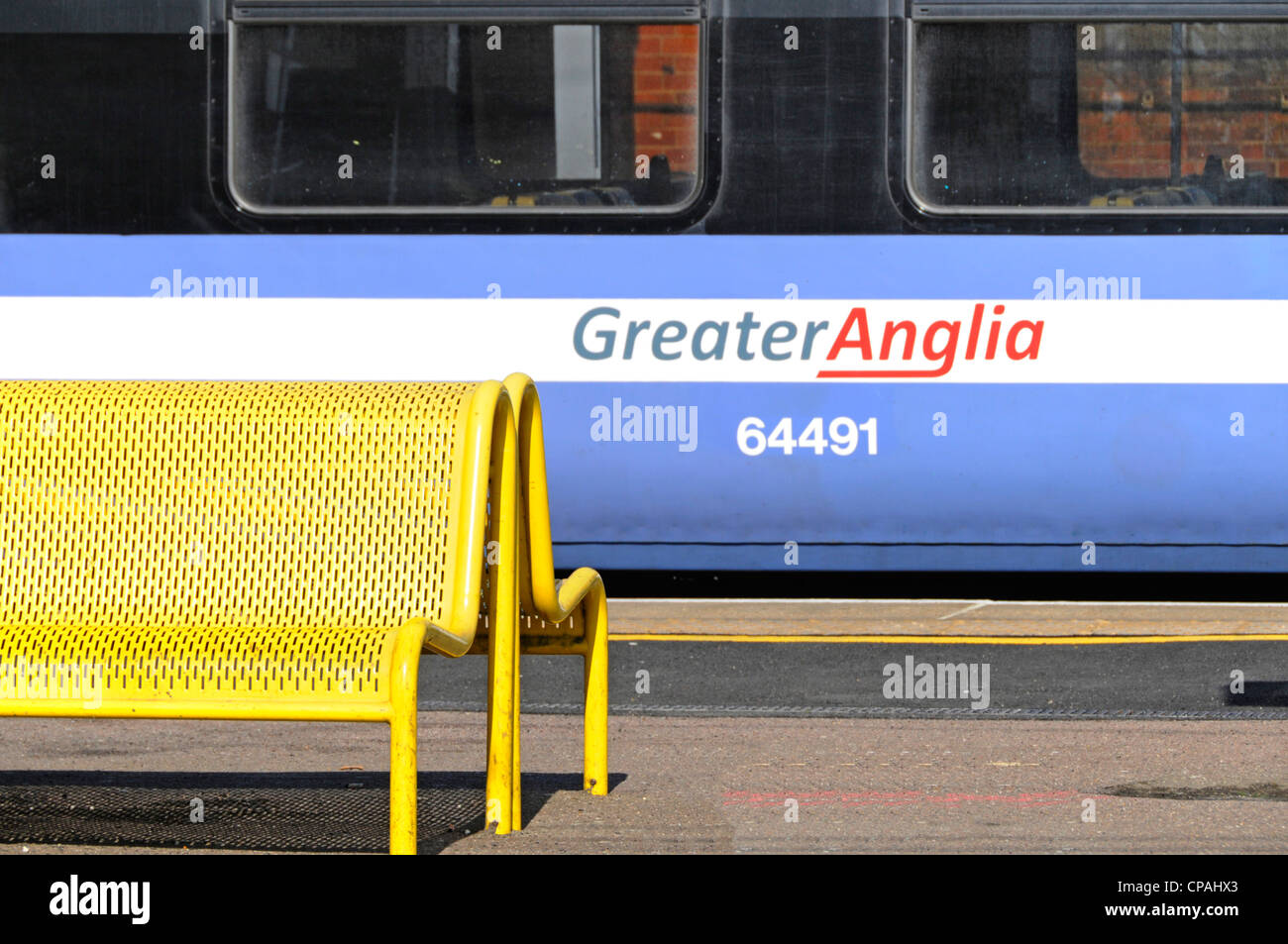 Train carriage Greater Anglia logo replacing the franchise previously operated by National Express waiting at train - Stock Image
