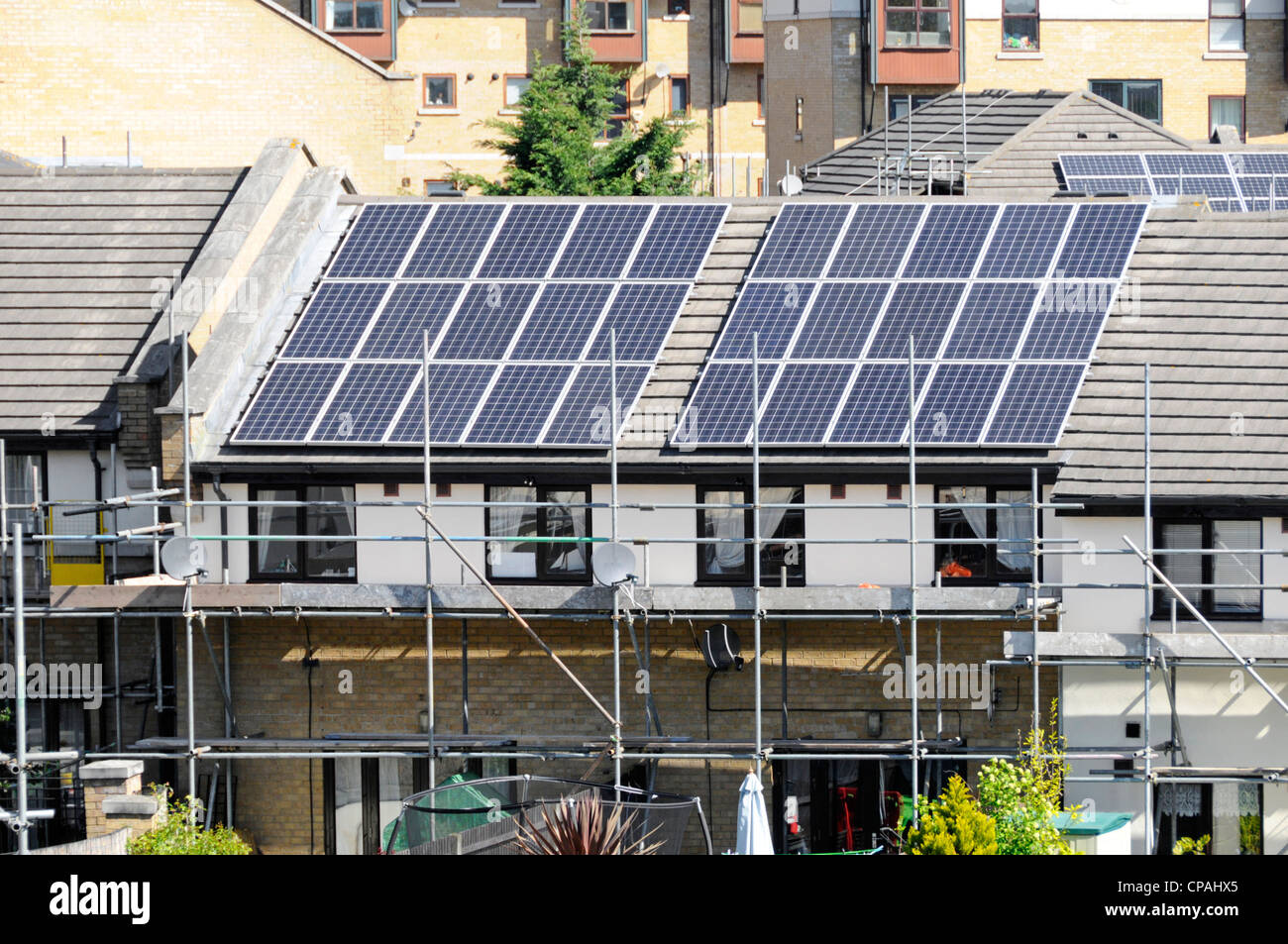Scaffolding for solar energy power cell panels installation on roof of modern house for cheaper electricity Silvertown - Stock Image