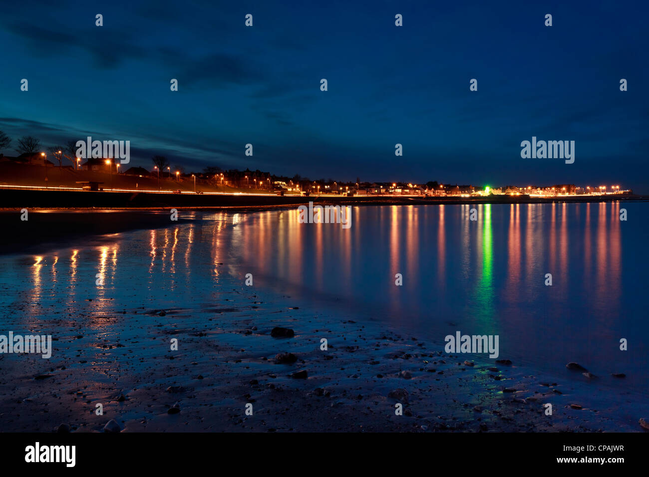 Rhos on sea at night with the street lights reflected in the evening waters. Stock Photo