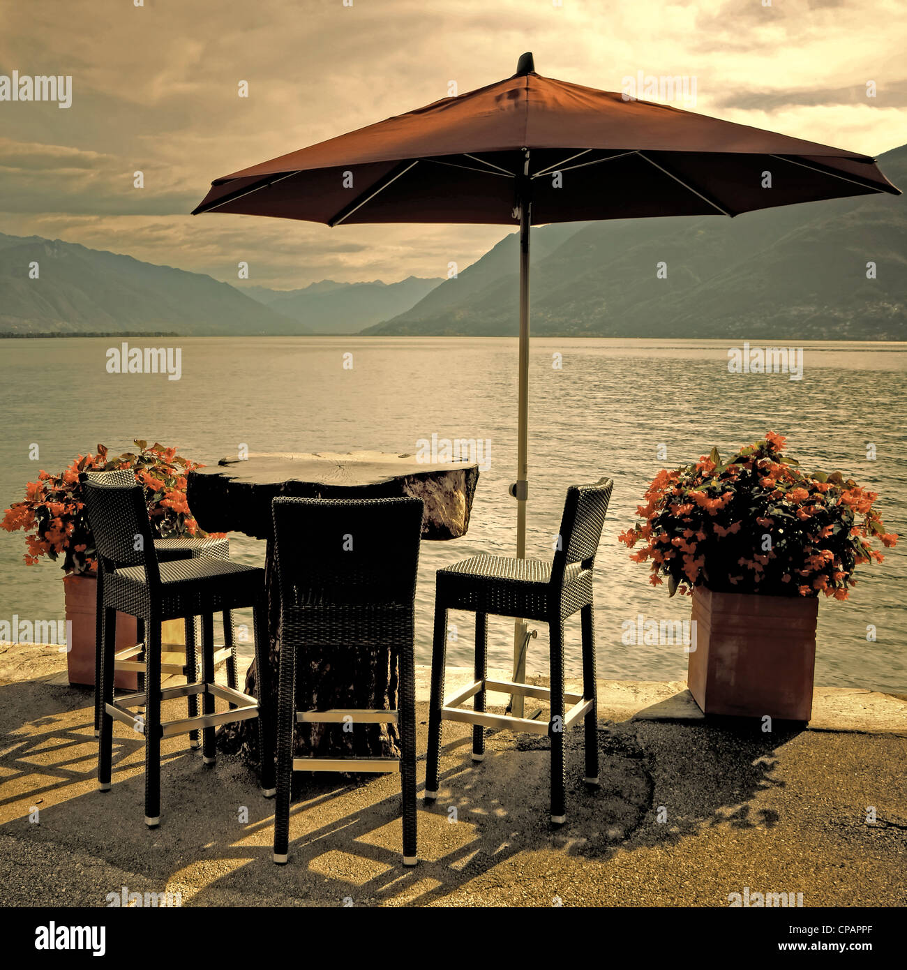 table, chairs and parasol at the Lake Maggiore in Brissago, Ticino, Switzerland - Stock Image
