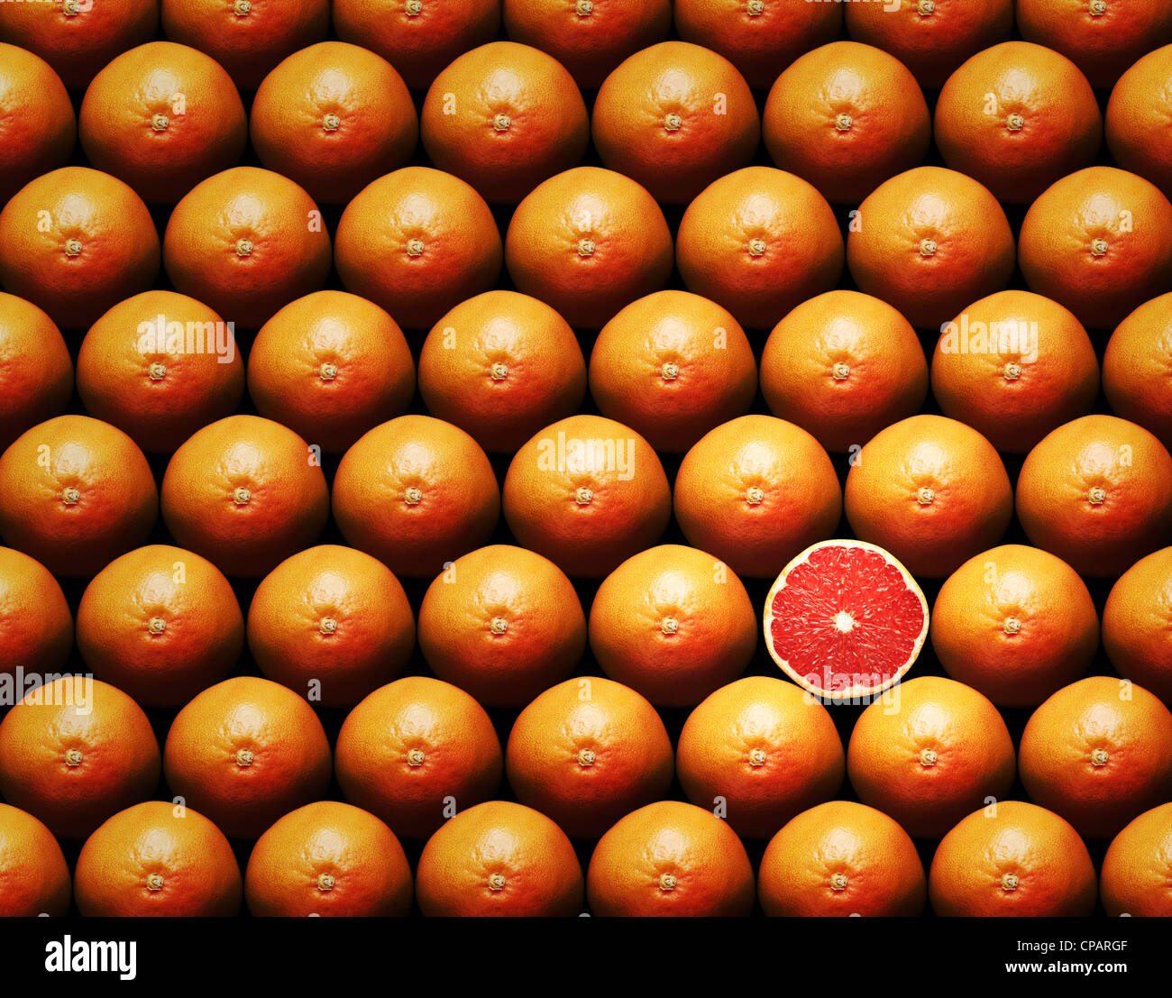 Grapefruit slice amongst many whole grapefruits - Stock Image