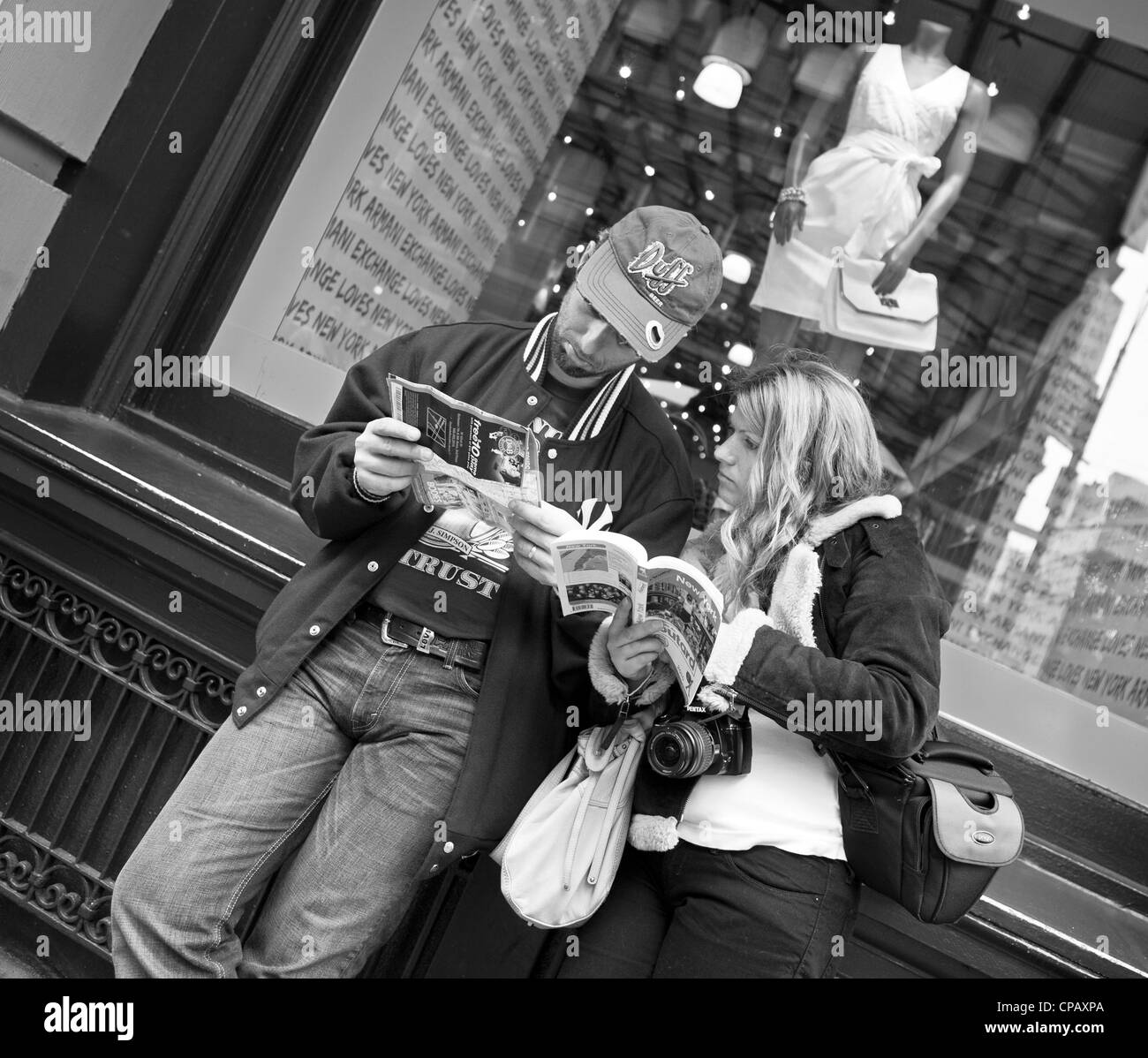 A couple of tourists in New York City try to decide what to do next. - Stock Image