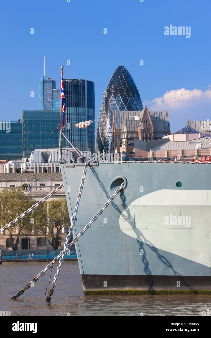 Bow of HMS Belfast and city buildings; London; England - Stock Image