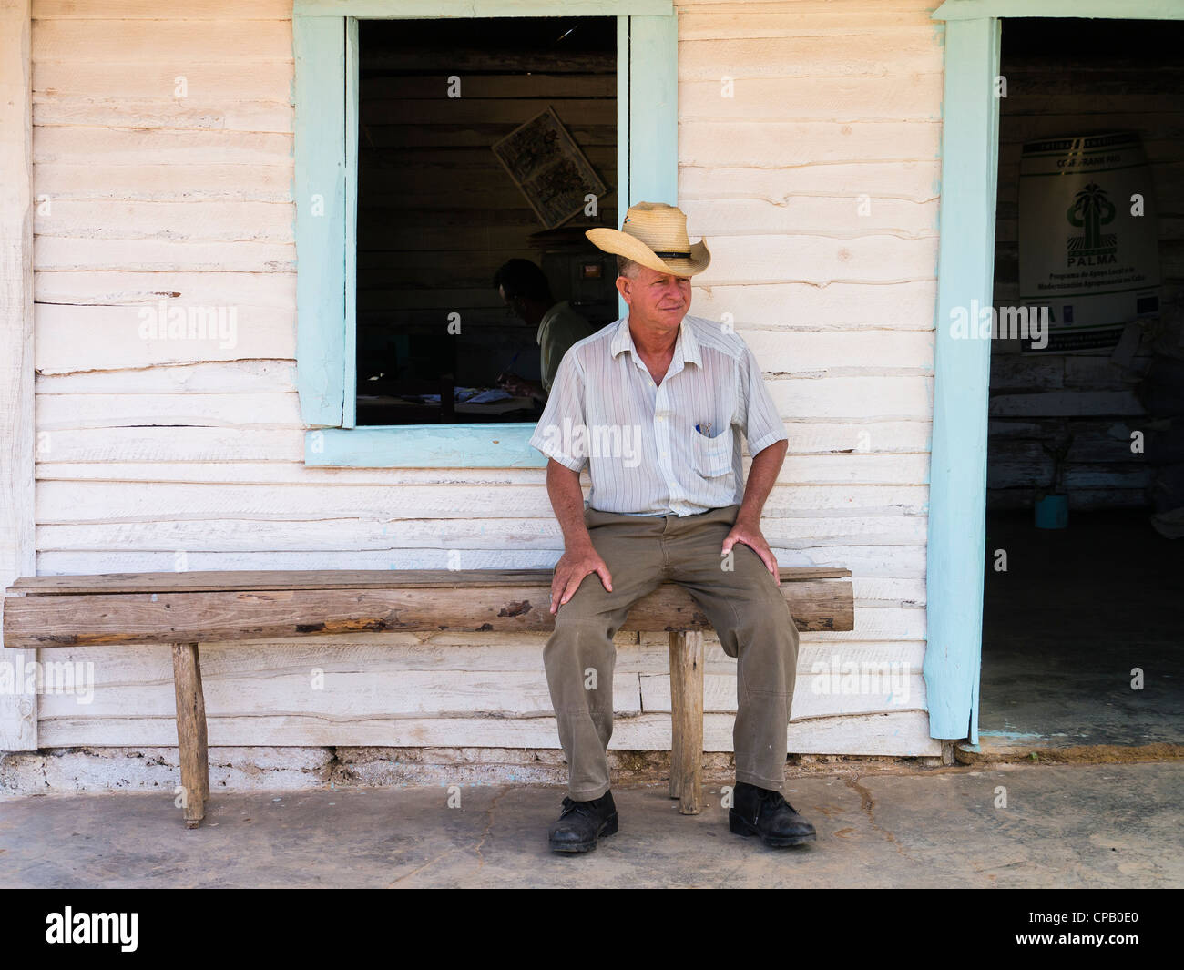 A 60-70 year old Cuban Hispanic male sits on a crude wooden bench on his front porch wearing a straw hat in Viñales, Cuba. Stock Photo