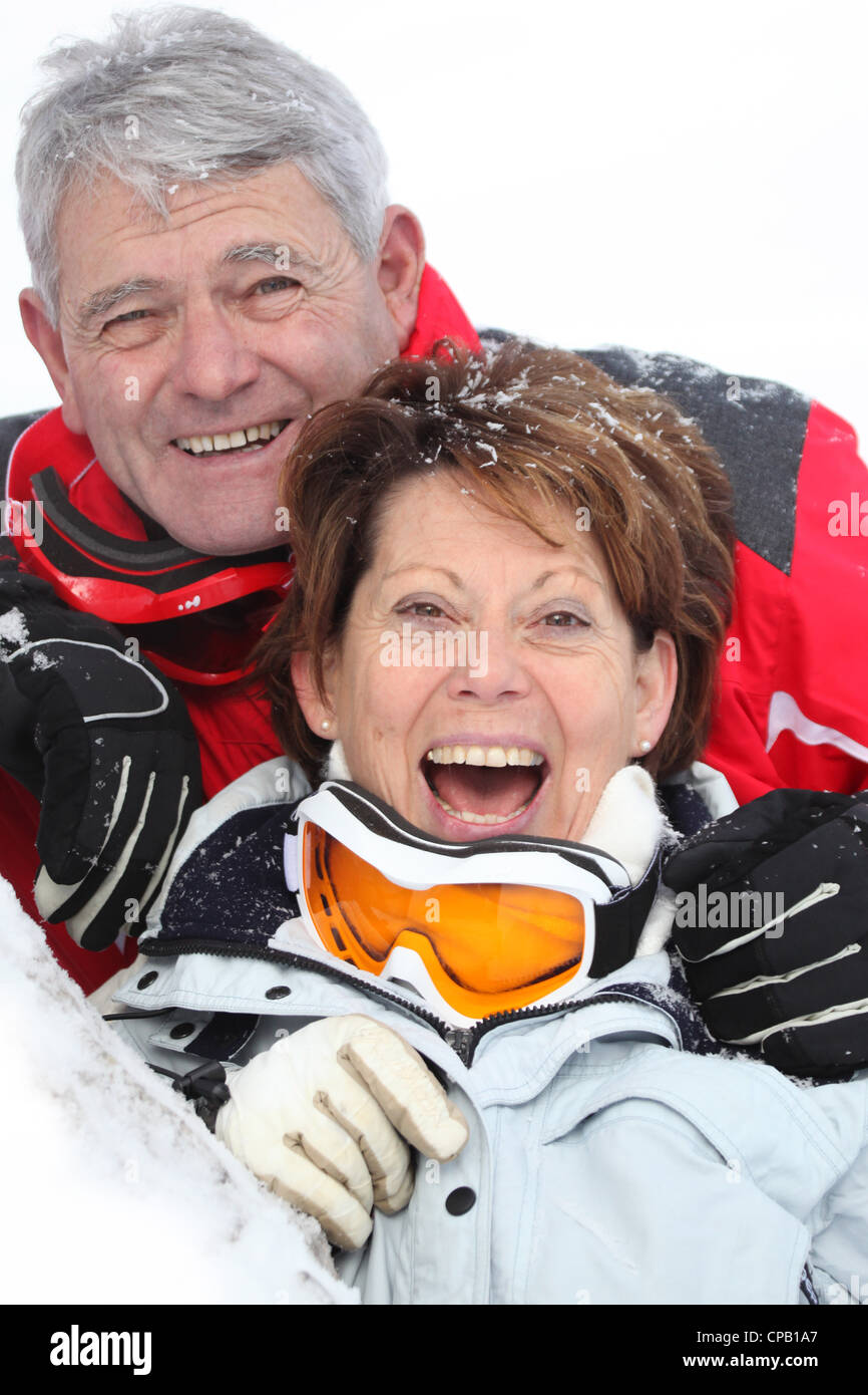 Senior couple having a great time skiing - Stock Image