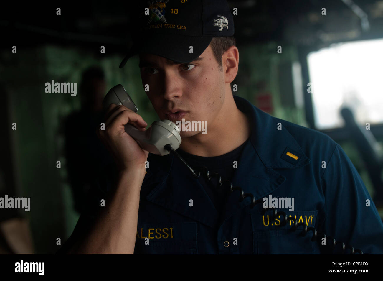 Ensign Thomas Alessi relays information through a sound powered telephone in the pilothouse of the amphibious transport - Stock Image