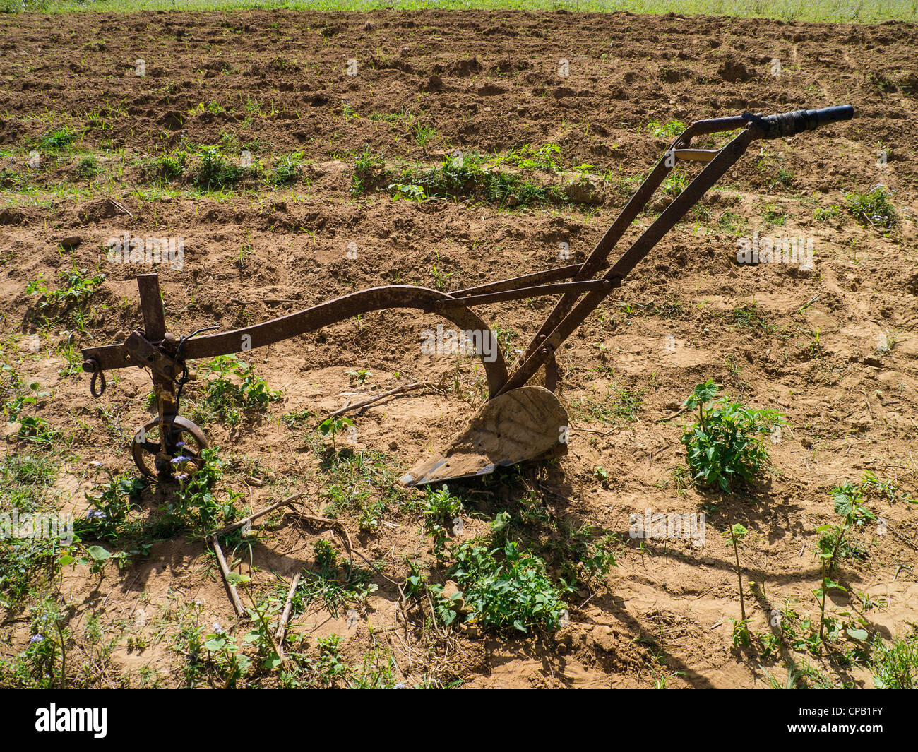 A primitive horse or ox drawn plow sits in a barren tobacco field in Viñales, Cuba. - Stock Image