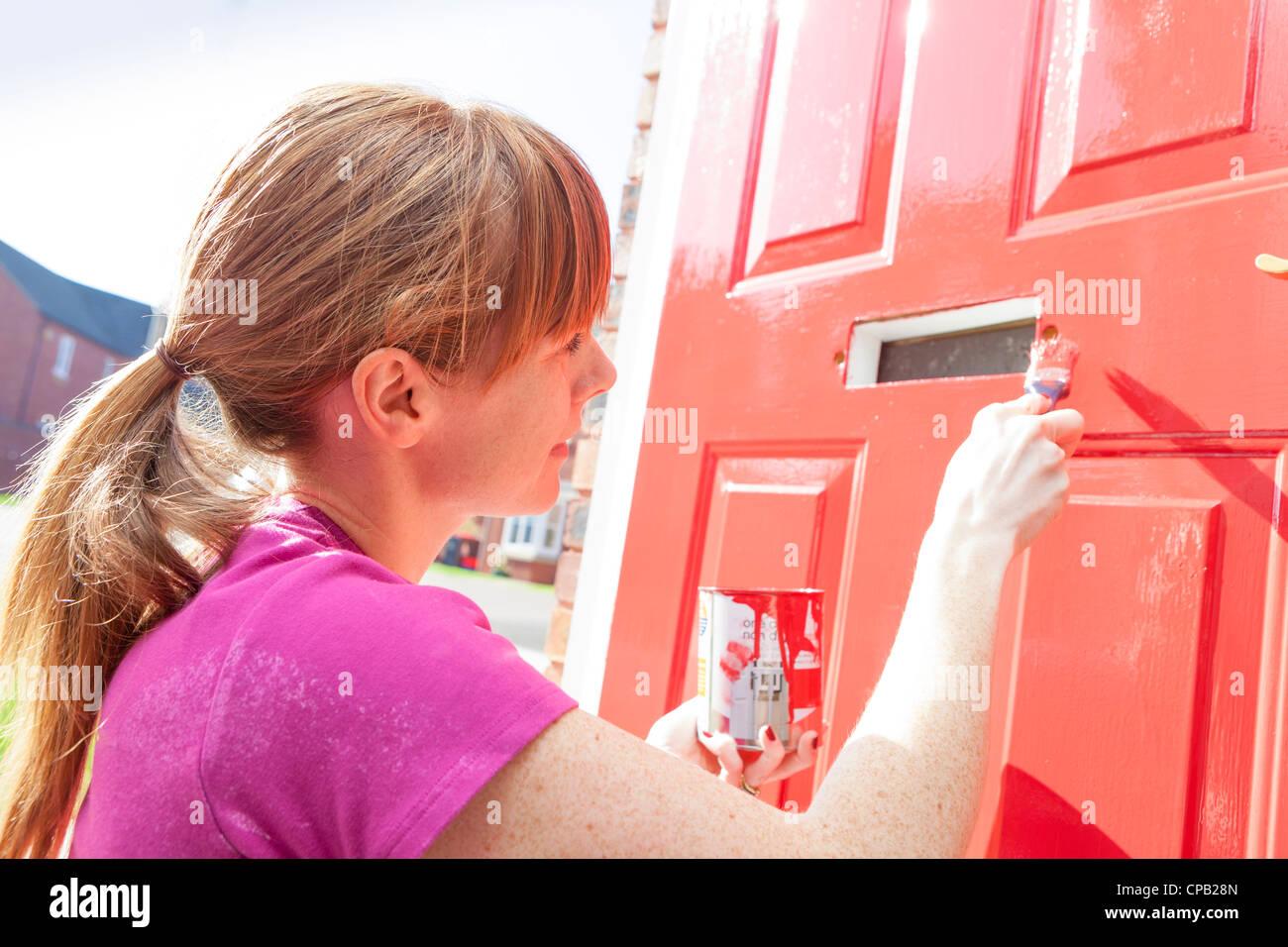 Woman in her thirties painting her front door red. Stock Photo