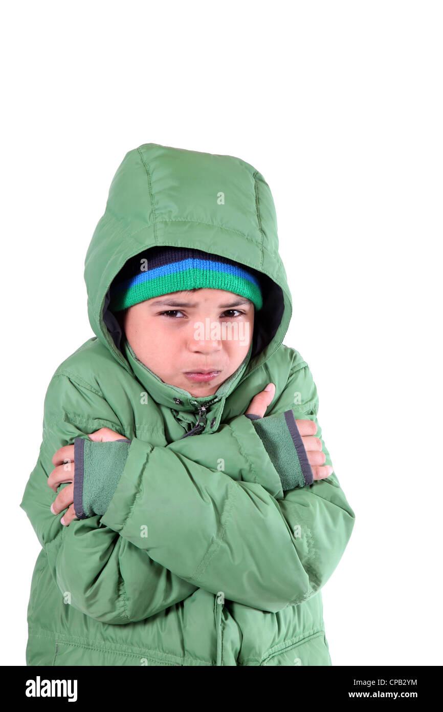 studio shot of a hispanic boy shivering in winter gear stock photo