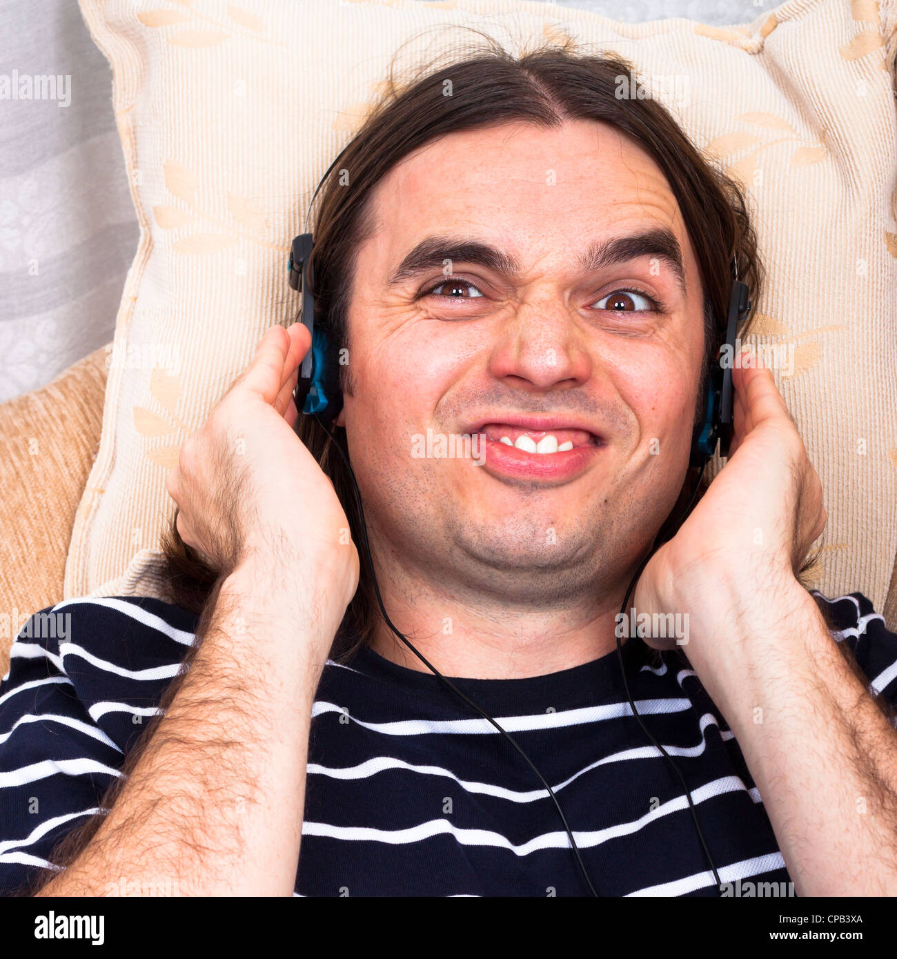 Young Funny Man With Headphones Listening Music On Sofa