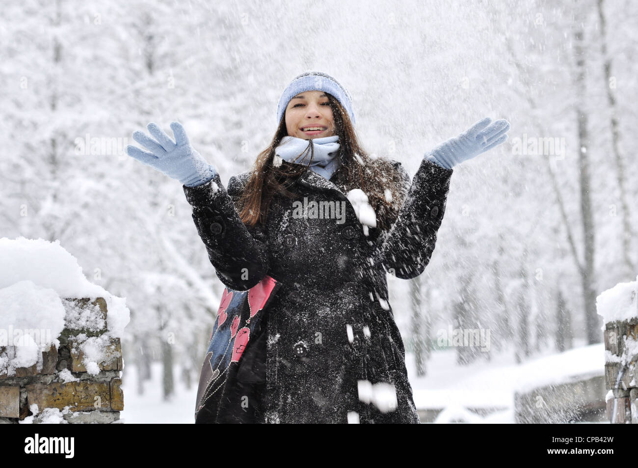 beautiful girl throwing snow in the air in winter park - Stock Image
