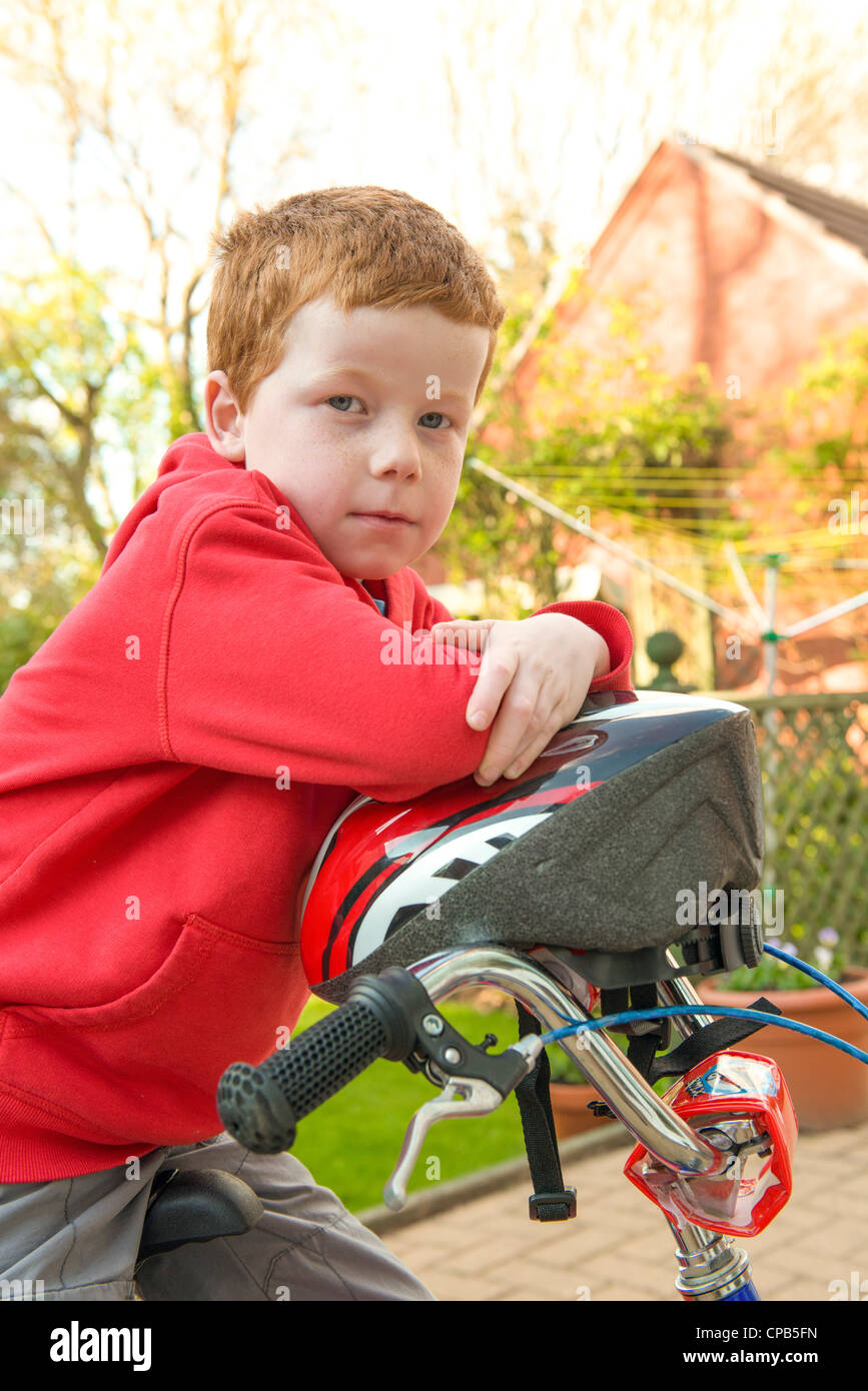 Little boy on his bike in his garden, looking to camera. - Stock Image