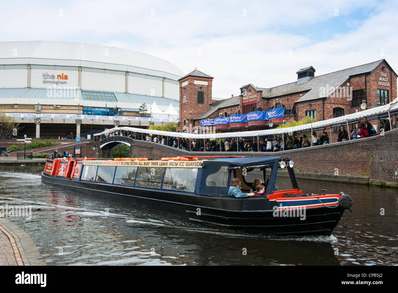 A canal barge passes the National Indoor Arena during a conference at the venue. - Stock Image