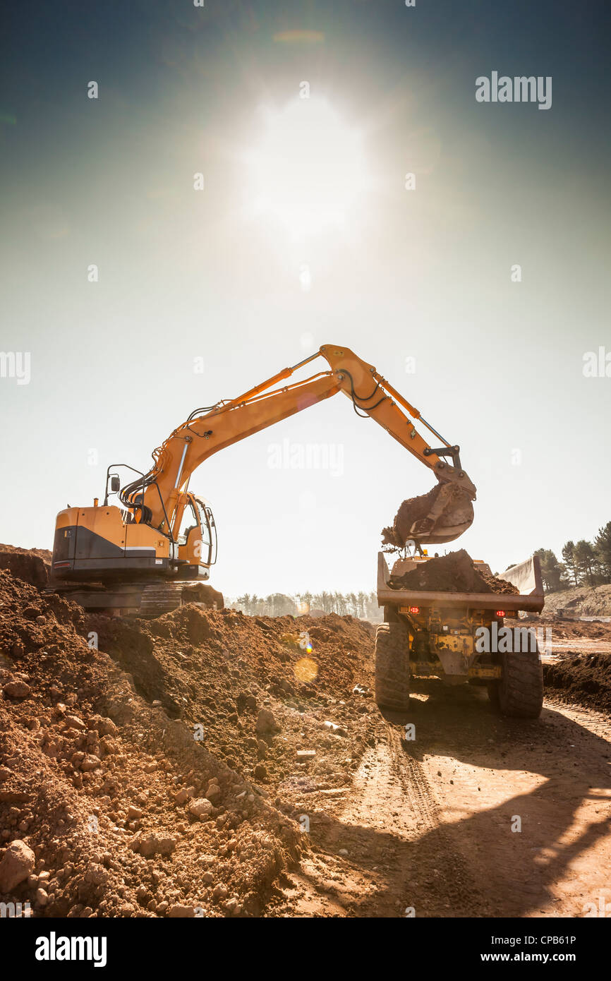 Land clearance on a construction site. Digger filling a lorry with soil. - Stock Image