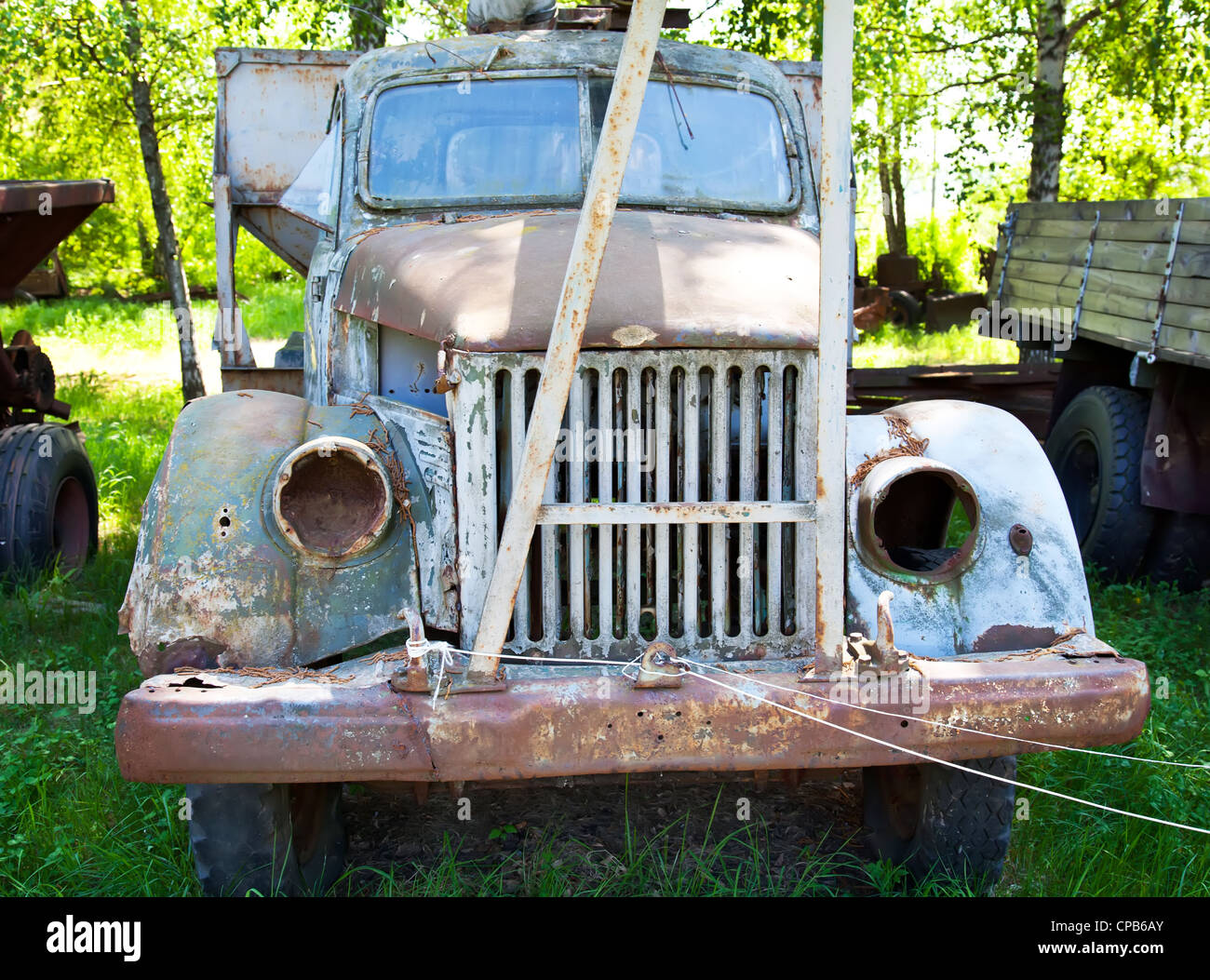 Old obsolete vehicle without lights on green grass - Stock Image