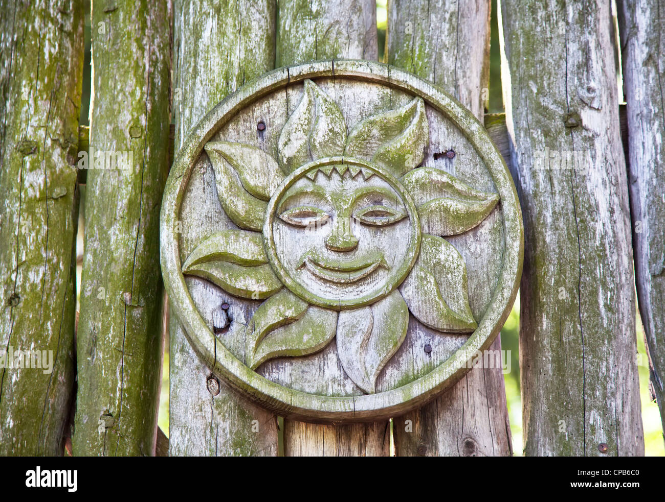 Pagan wooden sun sign on a log - Stock Image