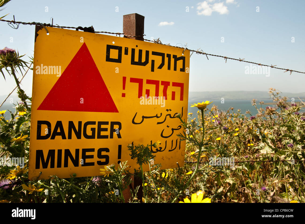 "A sign reading ""Danger Mines!"" hangs from a barbed wire fence in the Israeli occupied Golan Heights. Stock Photo"