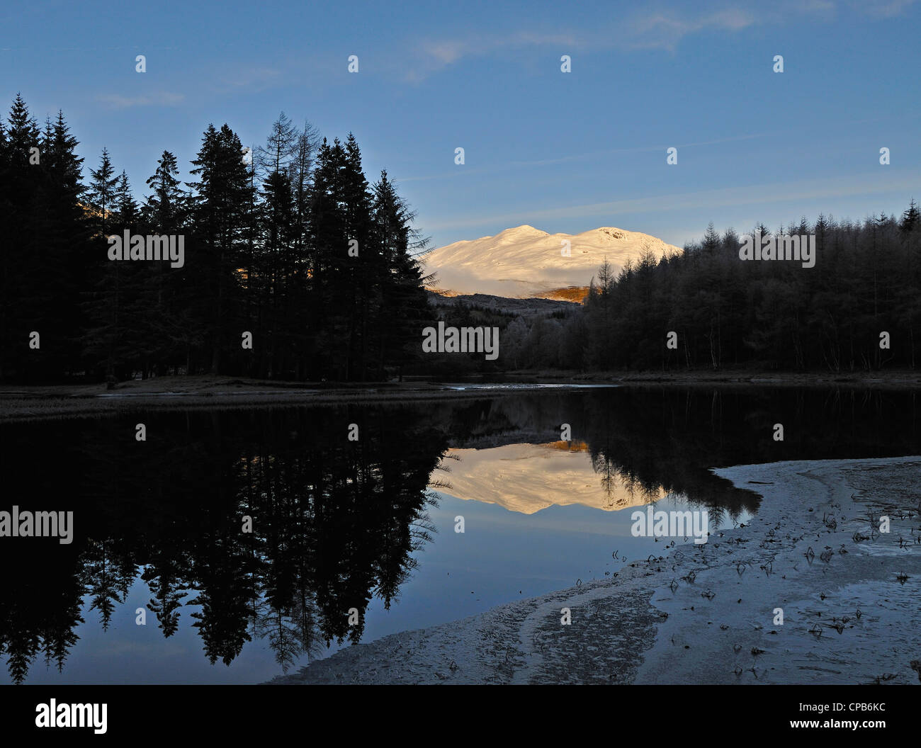 A quiet stretch of the River Dochart reflects conifer woods and a distant snowy mountain in Glen Dochart, Perthshire, - Stock Image