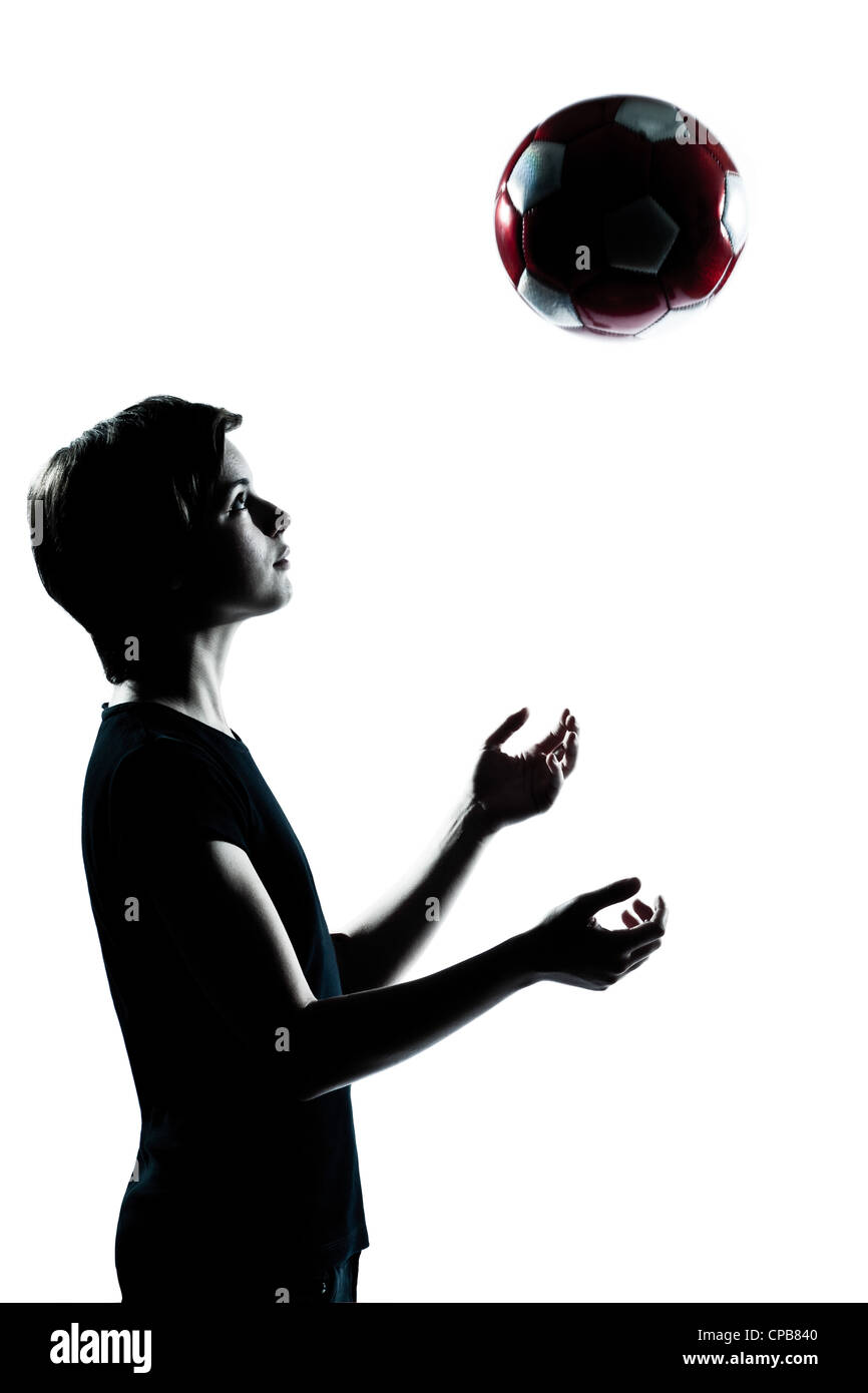 one caucasian young teenager silhouette boy girl tossing soccer football portrait in studio cut out isolated on - Stock Image