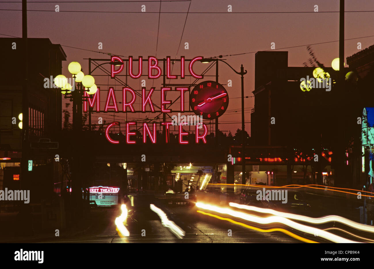 Retro Image, Sunset At The Pike Place Market With Neon Signs And Clock  Illuminated With Traffic Car Light Streaks Seattle