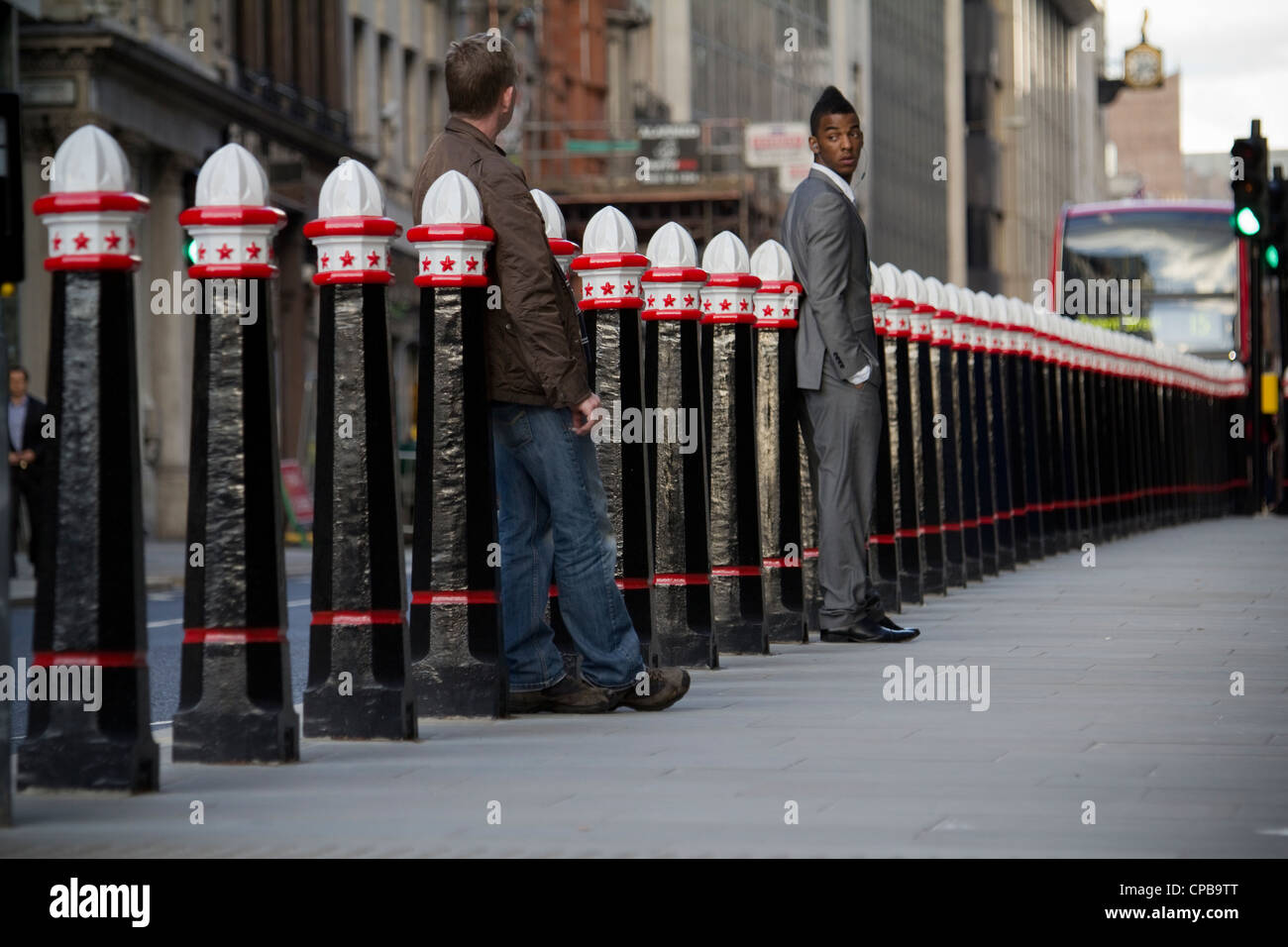 Men waiting by, Freshly painted City of London Bollards outside Cannon street station - Stock Image