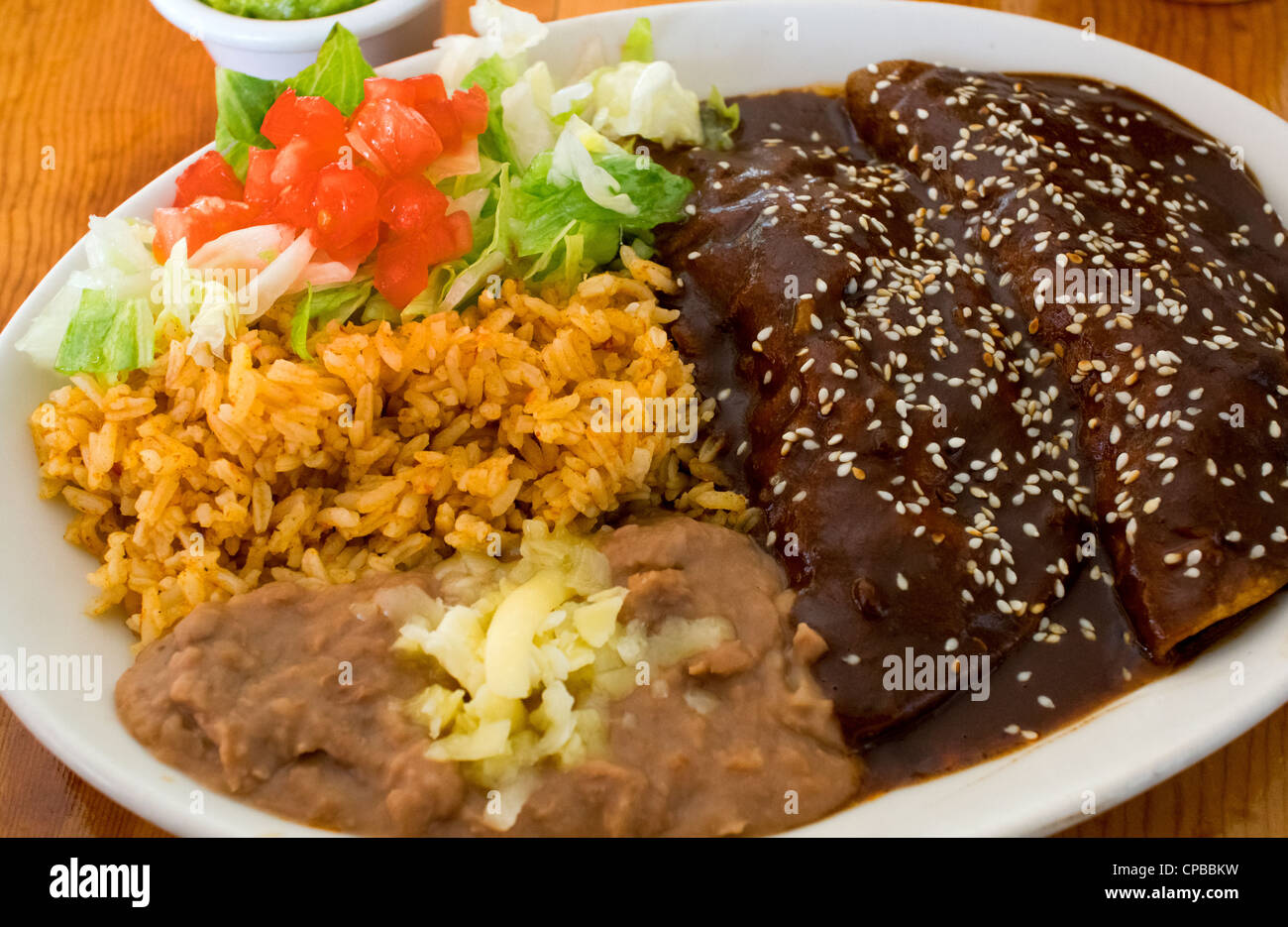 Enchiladas mole with rice and beans with cheese and salad ...