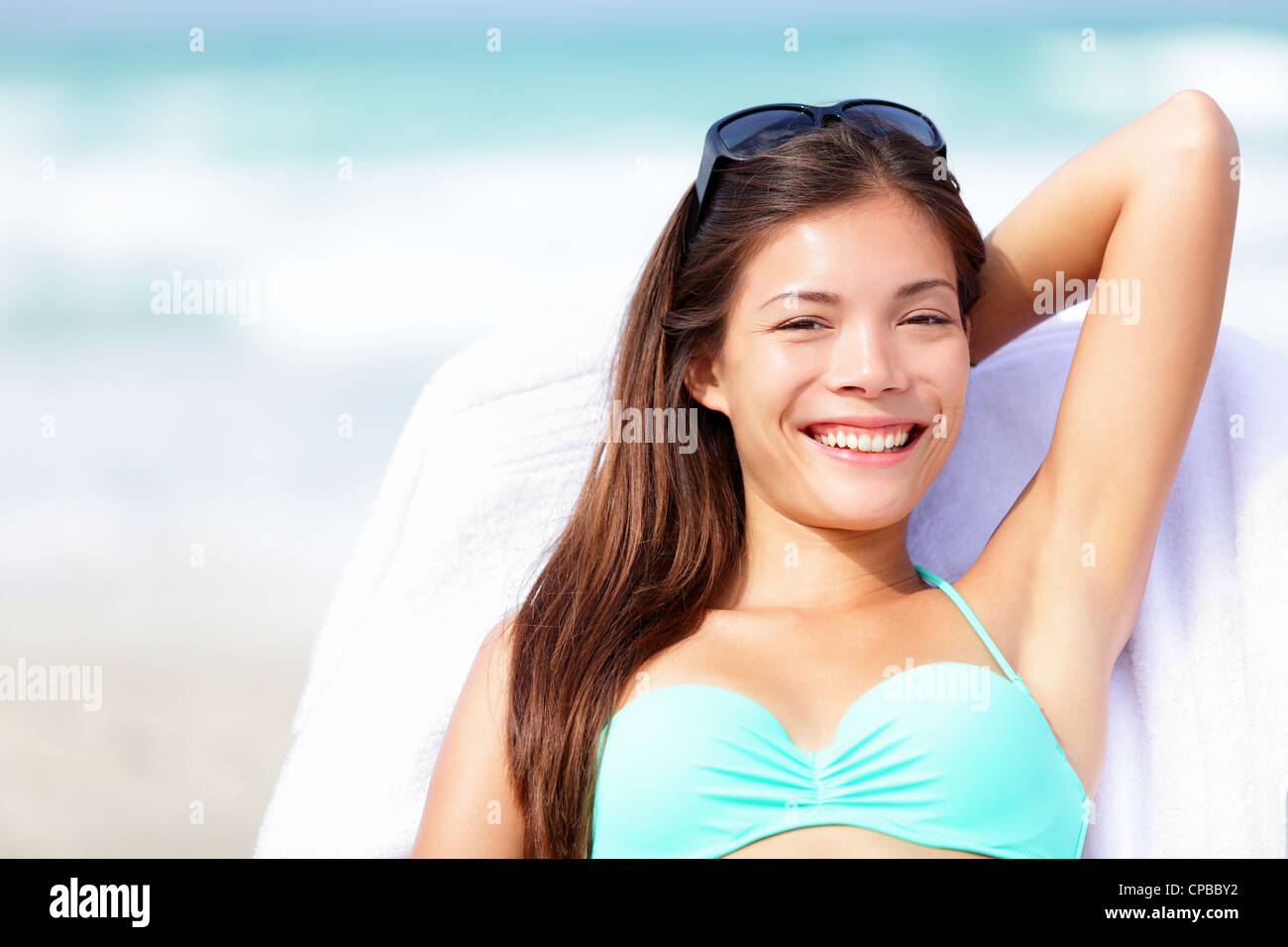 Portrait of beautiful young multiracial Caucasian / Asian Chinese woman enjoying summer holidays relaxing on sunbed - Stock Image