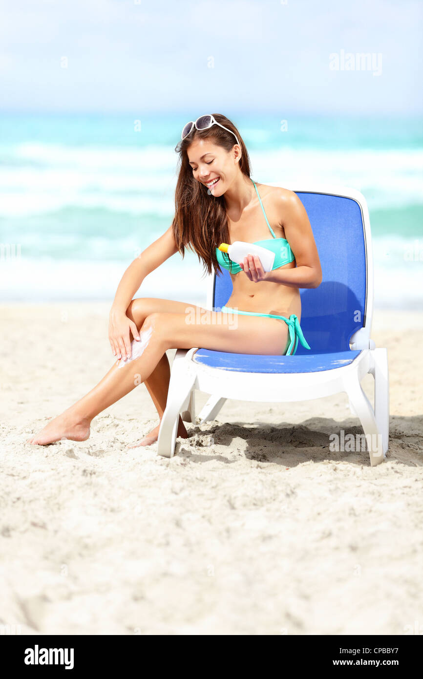 Beautiful young mixed race woman in bikini applying sunscreen lotion on legs sitting on sunbed on Varadero Beach, - Stock Image