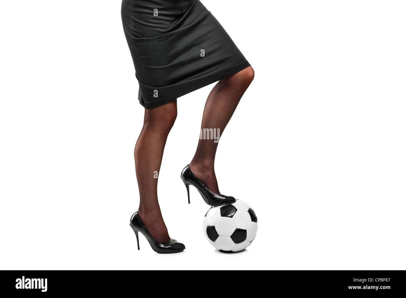 Woman in high heels standing on a soccer ball isolated on white background - Stock Image