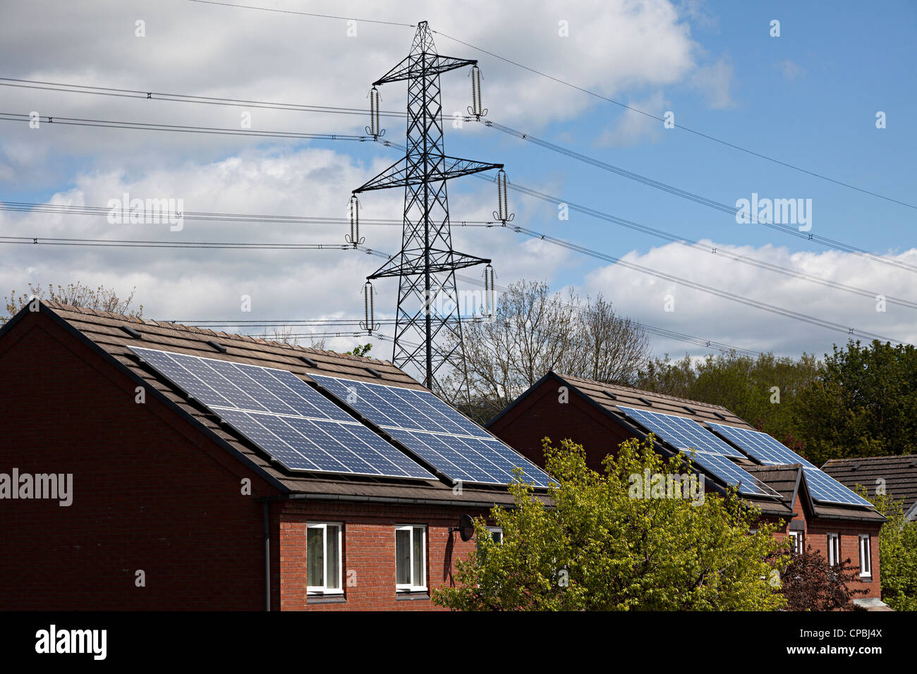 Solar panels on houses with electricity pylons behind, Wales, UK - Stock Image